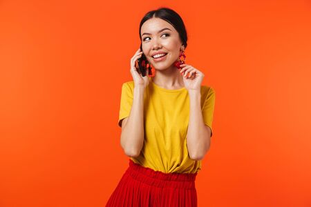 Image of a beautiful happy young woman posing isolated over orange wall background talking by mobile phone.
