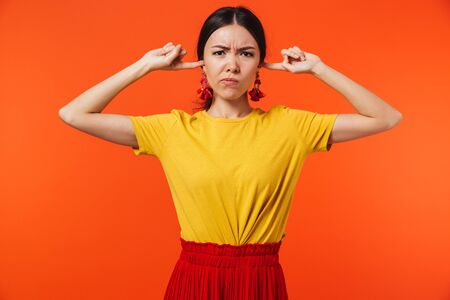Image of a beautiful displeased young woman posing isolated over orange wall background covering ears.