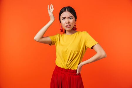 Afbeelding van een mooie verwarde ontevreden jonge vrouw poseren geïsoleerd over oranje muur achtergrond. Stockfoto