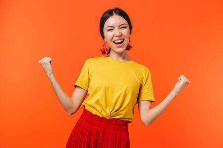 Das Bild einer schönen aufgeregten, glücklichen jungen Frau, die isoliert über orangefarbenem Wandhintergrund posiert, macht Siegergeste.