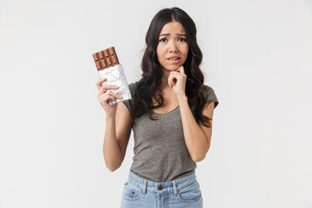 Image of displeased girl 20s dressed in basic clothes holding chocolate bar isolated over white background in studio