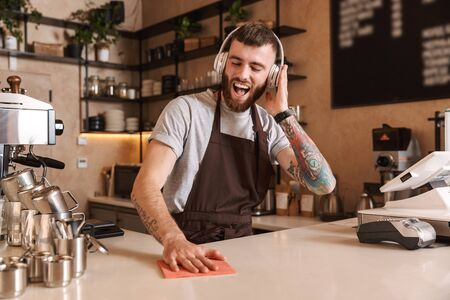 Smiling attractive man barista standing behind the counter at the coffee shop, listening to music with headphones Фото со стока