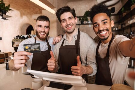 Three cheerful men baristas standing behind the counter at the coffee shop, taking a selfie, showing credit card 写真素材