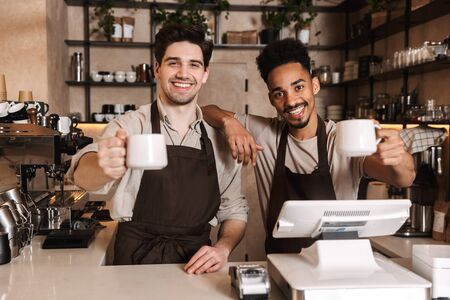 Image of two happy coffee men colleagues in cafe bar working indoors. 스톡 콘텐츠