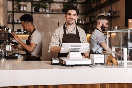 Image of three happy coffee men colleagues in cafe bar working indoors.