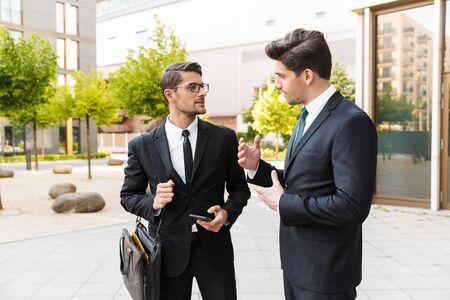 Dos atractivos hombres de negocios jóvenes confiados con trajes de pie al aire libre en las calles de la ciudad, discutiendo un nuevo proyecto