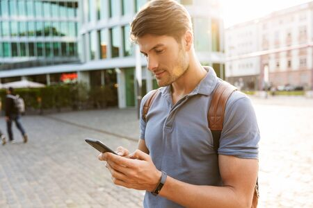 Handsome young man dressed casually spending time outdoors at the city, carrying backpack, using mobile phone