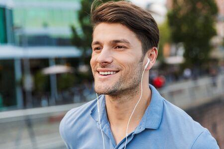 Apuesto joven sonriente vestido casualmente pasar tiempo al aire libre en la ciudad, escuchando música con auriculares Foto de archivo