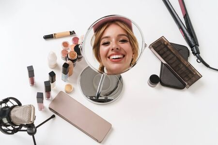 Close up of a beautiful young smiling girl blogger wearing cap doing makeup while looking at the mirror, sitting at the table isolated