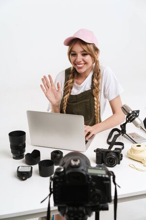 Image of funny girl recording blog broadcast with microphone about new professional photocamera and technics isolated over white wall in studio