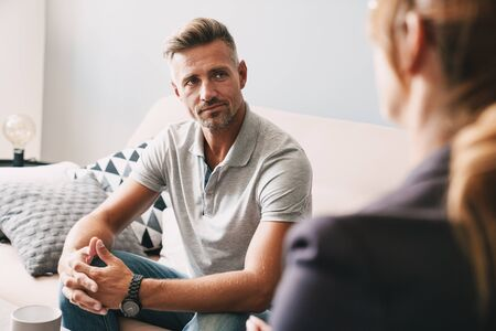 Photo of confident focused man having conversation with psychologist on therapy session in room