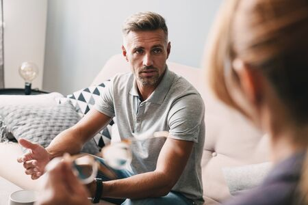Photo of brooding handsome man having conversation with psychologist on therapy session in room