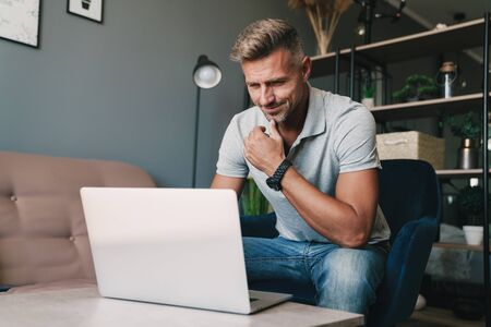 Photo of successful caucasian man in casual clothing using laptop while sitting on armchair at home Standard-Bild
