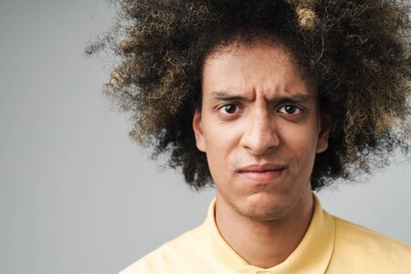 Photo closeup of uptight caucasian man with afro hairstyle frowning at camera with sad look isolated over gray background Stock Photo