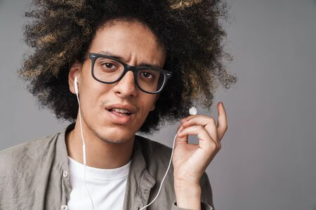 Photo closeup of young puzzled man with afro hairstyle looking at camera and using earphones isolated over gray background