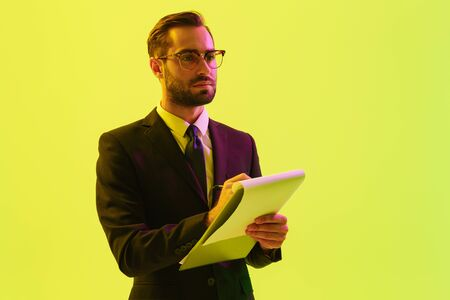 Photo of a serious handsome young business man posing isolated over light green background wall with led neon lights holding clipboard writing notes.