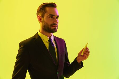 Handsome confident young businessman wearing formal suit standing isolated over yellow background, smoking electronic cigarette