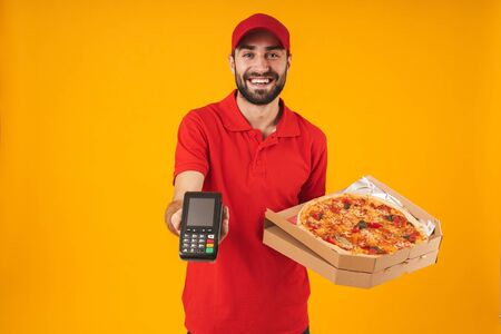Photo of attractive delivery man in red uniform holding pizza box and payment terminal isolated over yellow background