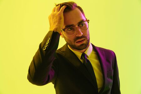 Picture of a handsome serious business man posing isolated over light green background wall with led neon lights.