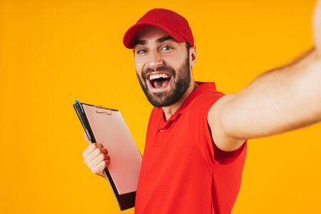 Portrait of excited delivery man in red uniform smiling and holding clipboard while taking selfie photo isolated over yellow background