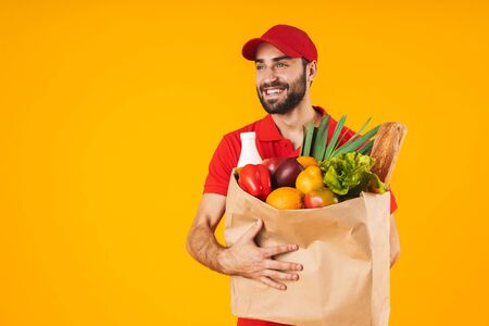 Portrait of attractive delivery man in red uniform smiling while carrying paper bag with food products isolated over yellow background