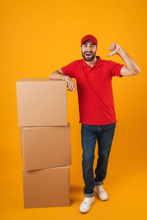 Portrait of joyful delivery man in red uniform pointing fingers at himself while standing with packaging boxes isolated over yellow background