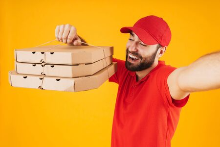 Portrait of positive delivery man in red uniform smiling and holding takeaway pizza boxes while taking selfie photo isolated over yellow background