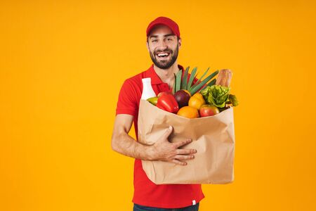 Portrait of pleased delivery man in red uniform smiling while carrying paper bag with food products isolated over yellow background