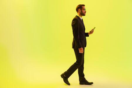 Beau jeune homme d'affaires portant un costume formel marchant isolé sur fond jaune, utilisant des écouteurs sans fil et tenant un téléphone portable