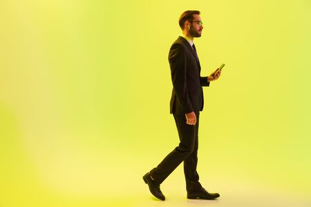 Handsome young businessman wearing formal suit walking isolated over yellow background, using wireless earphones and holding mobile phone