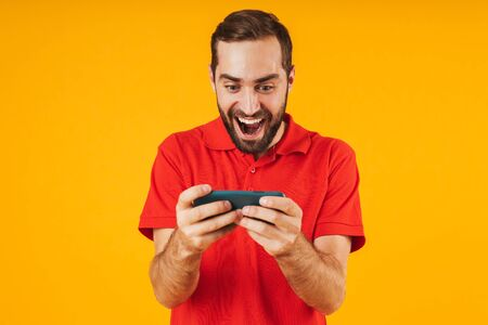 Portrait of handsome man in red t-shirt smiling and holding smartphone while playing video games isolated over yellow background