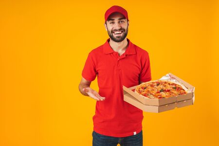 Photo of happy joyful man in red uniform smiling and holding pizza box isolated over yellow background Stockfoto