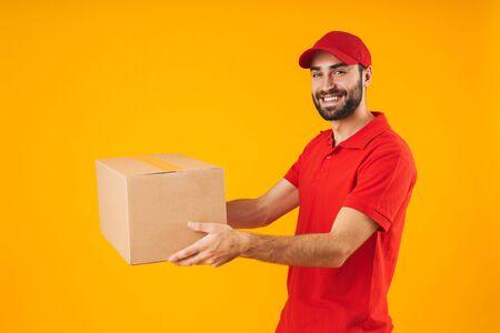Imagen de hombre de entrega satisfecho en uniforme rojo sonriendo y sosteniendo la caja de embalaje aislada sobre fondo amarillo Foto de archivo