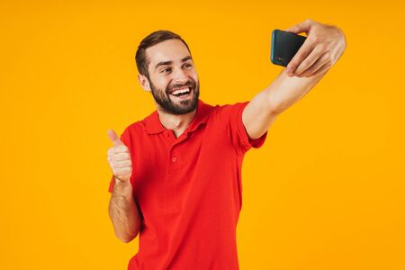 Portrait of attractive man in red t-shirt laughing and showing thumb up while taking selfie photo on cellphone isolated over yellow background Stockfoto