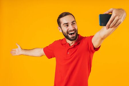 Portrait of young man in red t-shirt laughing and looking at camera while taking selfie photo on cellphone isolated over yellow background