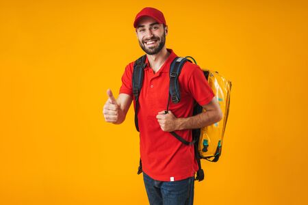 Photo of unshaven delivery man in red uniform showing thumb up and carrying backpack with takeaway food isolated over yellow background