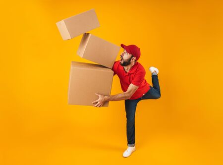 Full length portrait of shocked delivery man in red uniform carrying falling packaging boxes isolated over yellow background