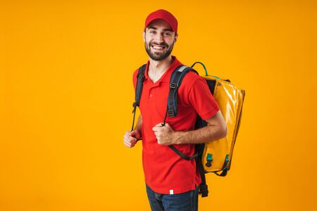 Photo of smiling delivery man in red uniform carrying backpack with takeaway food isolated over yellow background