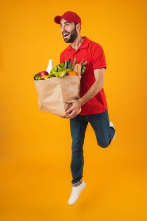 Portrait of happy delivery man in red uniform smiling while carrying paper bag with food products isolated over yellow background