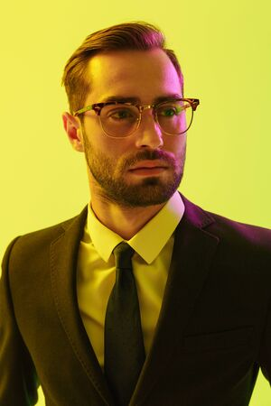 Photo of attractive young concentrated business man posing isolated over light green background wall with led neon lights. Stockfoto