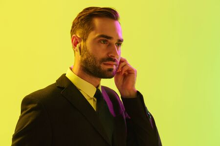 Close up of a handsome young businessman wearing formal suit standing isolated over yellow background, using wireless earphones