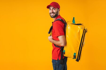 Photo of attractive delivery man in red uniform carrying backpack with takeaway food isolated over yellow background Stockfoto