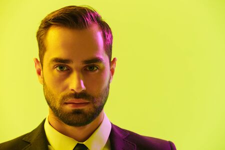 Image closeup of caucasian young businessman in formal suit looking at camera isolated over yellow background
