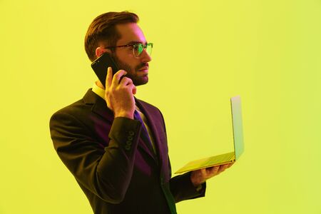 Photo of a serious young business man posing isolated over light green background wall with led neon lights using laptop computer talking by mobile phone.