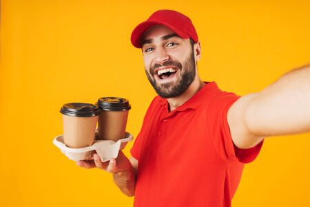 Portrait of cheerful delivery man in red uniform smiling and holding takeaway coffee cups while taking selfie photo isolated over yellow background Stockfoto
