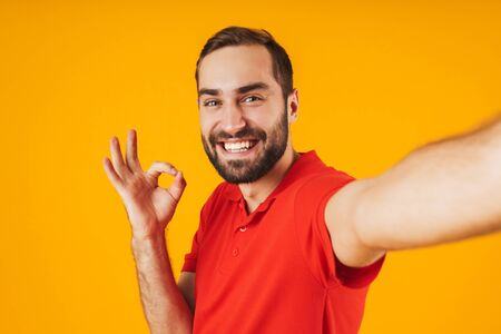 Portrait of happy man in red t-shirt laughing and showing ok sign while taking selfie photo isolated over yellow background