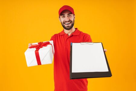 Portrait of excited delivery man in red uniform smiling while holding present box and clipboard isolated over yellow background Standard-Bild - 129805969