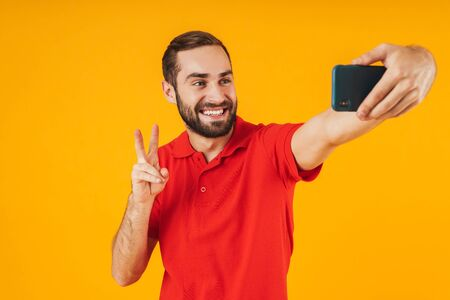 Portrait of unshaven man in red t-shirt laughing and showing peace sign while taking selfie photo on cellphone isolated over yellow background Stockfoto