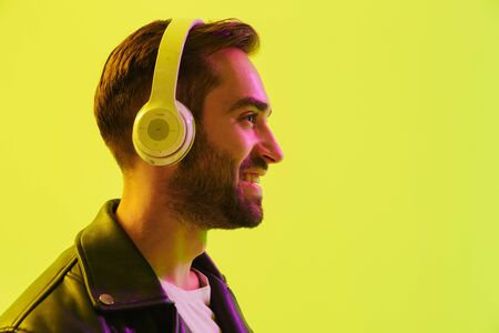 Close up side view of an attractive young man wearing leather jacket standing isolated over yellow background, listening to music with wireless headphones