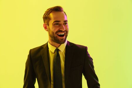 Image of excited young businessman in formal suit smiling and rejoicing isolated over yellow background